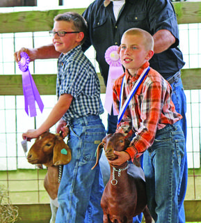Caleb Miller and Jamie Grimes show off their winning goats.