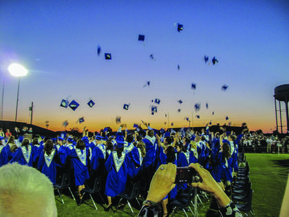 The new graduates tossed their caps into the air after the ceremony.