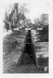 "WPA workers installed sewer pipe on Water Street in Hodgenville, circa 1934-1942. The ""old mule barn is at right."""
