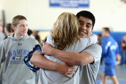 Ed Hernandez, LaRue County's 182-pound wrestler, was congratulated by Missy Metcalf, his former preschool teacher, after he won a key victory Saturday for his team during the Region 2 tournament.