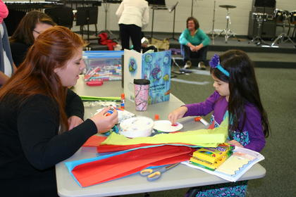 Charley Hemsley, a student at Campbellsville University, helped Claire Higginbotham, 6, craft a rainbow fish at the Extension Expo. She was working with the LaRue County Early Childhood Council, offering developmental screenings for children.