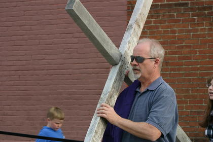 Tony Simon carries the cross.