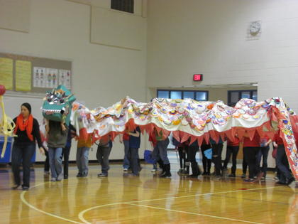 "Fifth-grade teacher Laura Kudrna carries the ""Pearl of Wisdom"" as she leads the Chinese Dragon into the HES gym. Students cheered loudly to provide enough noise to wake the dragon."