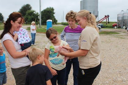 Leanne Ragland shows off one of Shady Rest Farm's piglets to a group at AGstravaganza.