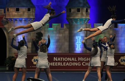 Emily Armes and Grace Armes soar through the air during a transitional stunt in National finals. Bases are Taylor Dawson, Kristen Kells, Savannah Long, Mallory Skaggs, Allyson Hutchins and Gabriela Garcia.