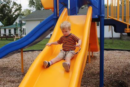 Ronan Byrne, 2, of Louisville slides down the slide