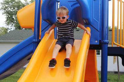 Kieran Byrne, 5, of Louisville slides down the slide
