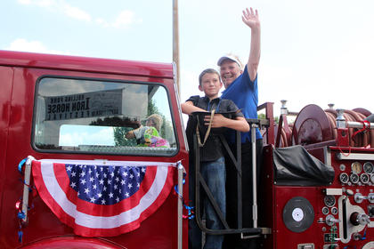 Braden Sferro throws candy to the crowd from a fireman's helmet while riding an antique fire engine with Jane Masse.