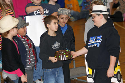 "Nicholas Hardin accepts a fruitcake from Dillon Wayne as Page Evans, Pablo Hernandez, and Brian Sanchez watch while Mrs. Weaver's class sings ""Everlasting Fruitcake."""