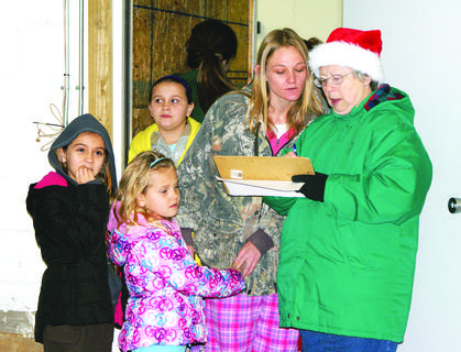 Linda Daniels, a volunteer for Santa's Helpers, took down names, ages and sizes of children who were receiving gifts from the Santa Bus. Jamie Underwood and her children, Charity Meredith, 6, and Hope Meredith, 8, wait their turn.