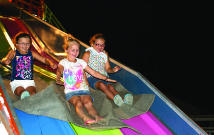 Chandler Moreland, Carsen Moreland and Larkin Knochel rode down the big slide Tuesday evening.