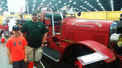 Bradley Laughner (Left) with his dad, John Laughner (Right)  posing with Elizabethtown antique fire truck at the Kentucky State Fair.
