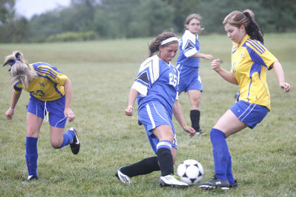 LaRue County High School senior Megan Smith navigated past Washington County High School defenders on Wednesday during the Lady Hawks' 7-0  victory against the Commanderettes in Willisburg.