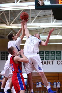 Hawks' Tyler Howell and Thomas Harman battled an Adair County player for a rebound in first round action of the 5th Region Tournament at Hart County.