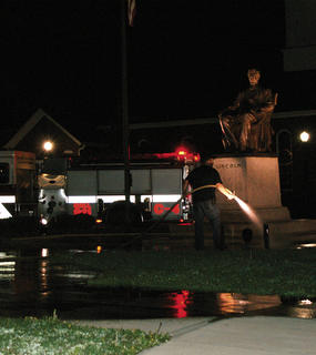 Jason Hodge, a LaRue County firefighter, used a fire hose to clean the Lincoln traffic island.