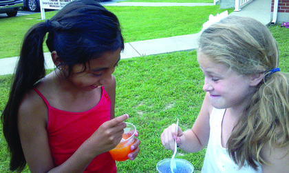 Macy Stillwell, left, and Chaley Warren cool off with snow cones during vacation Bible school at Pleasant Ridge Separate Baptist Church.