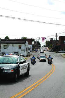 The motorcade escorted the hearse to the Taulbee family cemetery in Cecilia.