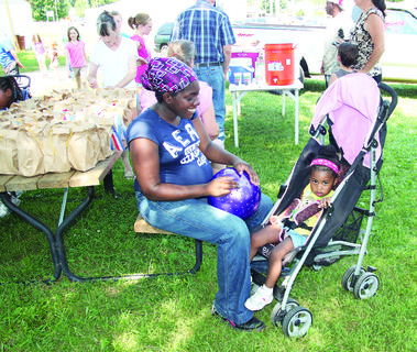 Mallory Thurman takes a moment to rest with daughter Andrea Johnson during Kids Day at the LaRue County Fair.