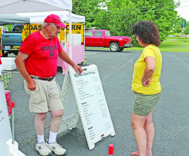 Beverly Sullivan checks out the prices at Nicky Durham's booth at the farmers market.