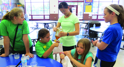 LaRue County students continued to have learning experiences at academic camps during summer break. Above, making fruit smoothies in plastic bags are, from left, Hayley Thompson, Yasmeen Hamada, Celeste Minard, MaKayla Phillips, and Emma Bowling.