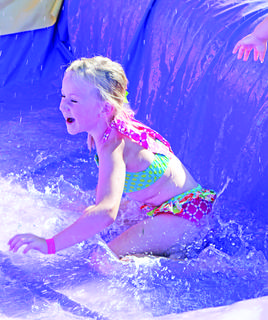 Coaches, parents and volunteers organized a fun day Friday for youth league sports teams. There were kickball, bouncy houses and water games.  In this photo: Brylee Dobson makes a splash after running through the sprinkler.