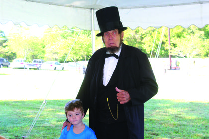 Longtime Abraham Lincoln presenter, Jim Sayre, pulled ALES kindergartner Hayden Haycraft from the crowd to play Austin Gollaher, who was Lincoln's childhood playmate that saved him from drowning. Haycraft played Gollaher while Sayre told the crowd the story.
