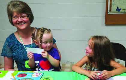 """Sitting in her mother's (Lisa Crim's) lap, Madison Crim """"discusses"""" some Bible information with her friend Julianne Heller at vacation Bible school held June 23-27 at Pleasant Ridge Separate Baptist Church."""