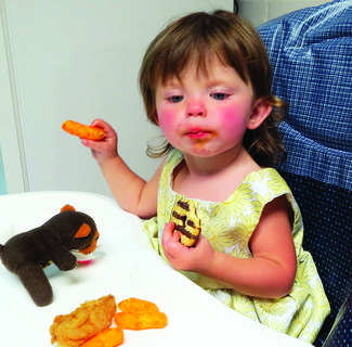 With a cookie in one hand, a Cheeto in the other, and her little bear keeping her company on her highchair, Lily Taulabee eyes what else might be ready to eat during a meal break at Pleasant Ridge Separate Baptist Church's vacation Bible school.
