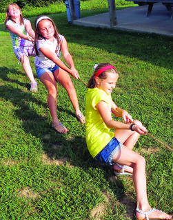 Fighting for every inch, the tug-of-war team (from the front) of Chaley Warren, Jocelyn Heller, and Allie Cecil strain against the rope at vacation Bible school June 23-27 at Pleasant Ridge Separate Baptist Church.