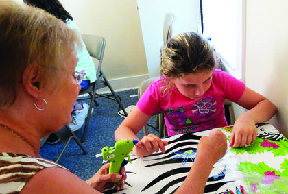 With glue gun in hand, Wanda Arnett helps her granddaughter Cynthia Polston create a flower magnet.