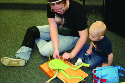 Morgan Milby helped 3-year-old Trentin Milby read a book at the kindergarten readiness screening.