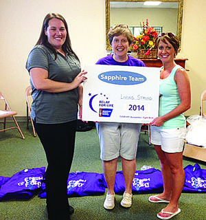 American Cancer Society representative Kristin Darrow congratulating Sapphire Team Living Strong captains Kathy Ross and Katie McDowell on $22,751.