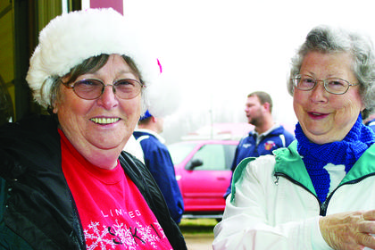 Ann Snookie Morrison and long-time Santas Helper Linda Daniels laugh as they go over the sign-in sheet.