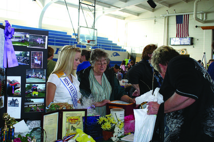 "Adrienne Poole, Miss Teen LaRue County Fair, assisted the LaRue County Fair Board members during the LaRue County Extension Expo. Ann ""Snookie"" Morrison is at right."
