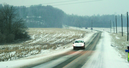 Traffic crawled on snowy roads Monday morning. Above, a snow-covered car drove down U.S. 31-E outside Hodgenville.