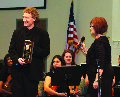 Diana Aubrey, right, a Hodgenville music instructor, presented Aaron Boaz, director of the Louisville Civic Orchestra, with a plaque honoring the group's 100th season. Aubrey and several other members of a planning committee spent several months organizing the concert.