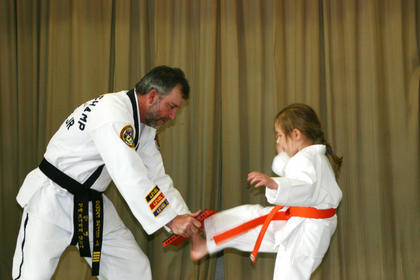 Instructor Randal Sallee Jr. encourages Madeline Reece, 5, of Elizabethtown, to break the board he is holding. Sallee, owner of Sallees Family Taekwondo in Hodgenville, put on a 45-minute demonstration with students.
