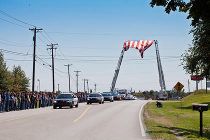 A large flag was lofted over the roadway near LaRue County High School. Several hundred students stood outside as the motorcade passed.