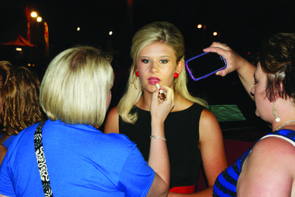 Family members put the finishing touch on Sheridan Mackenzie Elmore, 13, using the light of a cellphone to apply lipstick prior to the Miss Teen pageant. She is the daughter of Anthony and Jessica Elmore of Cecilia.