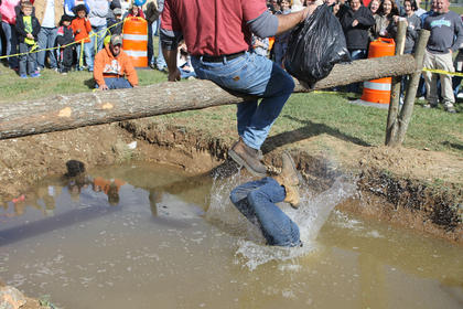 Tyler Adams lands face-down in the muddy pit after being defeated by Terry Davenport in a for-fun match on the pole ride.
