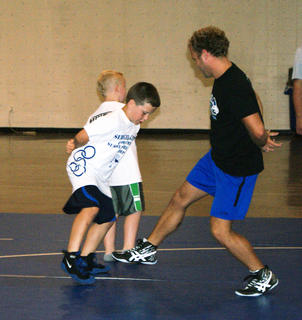 Coach Damon Barnes challenged Thomas Hoppes to foot tag during last week's Youth Wrestling Skills Camp.