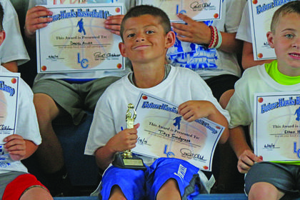 Titus Snodgrass smiled after he received a trophy and certificate at the conclusion of Future Hawks Basketball Camp