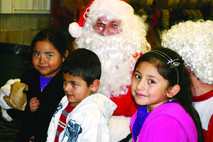 Miguel Salazar, 4, Leticia Salazar, 7, and Marlene Salazar, 5, sat in Santas lap at Magnolia Fire Department on Christmas Eve.