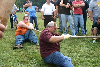 These two tug-of-war participants try to stabilize their team by getting all the way down on the ground.