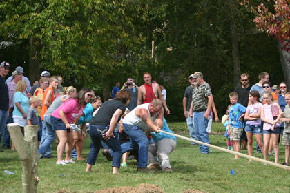 Crowd members and supporting friends and family cheer a tug-of-war team on during the second round of the tug-of-war competition on Saturday. Above, Ray Nunn gives his best effort while his wife Megan encourages him.