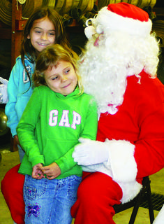 Charity Meredith, 4, and her sister Hope Meredith, 7, visited with Santa and Mrs. Claus inside Magnolia Fire Department on Christmas Eve.