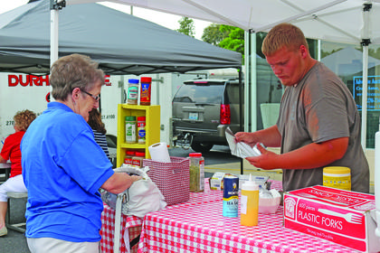 Wanda Skaggs purchases roasted corn from Forrest Durham. The farmers market will be open from noon to 6 p.m. every Thursday in July.