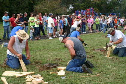 Water boil relay participants begin chopping wood planks to make their fires.