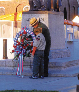 Cub Scout Cody Burd and William Justice, superintendent of Abraham Lincoln Birthplace National Historic Park placed a wreath at the foot of the Lincoln statue.