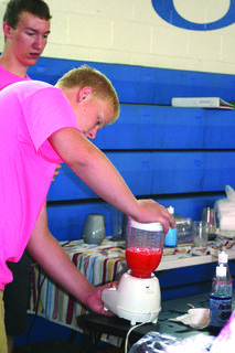 "Wyatt Long making slushies at the ""snowy Confections"" booth."